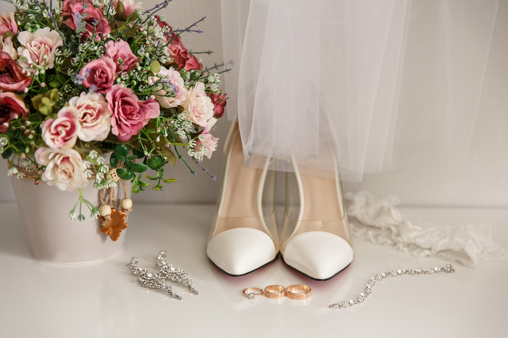 Bridal accessories for luxury wedding day. Marriage concept. Wedding and engagement ring near shoes on high heels, jewelry for bride and bouquet of flowers
