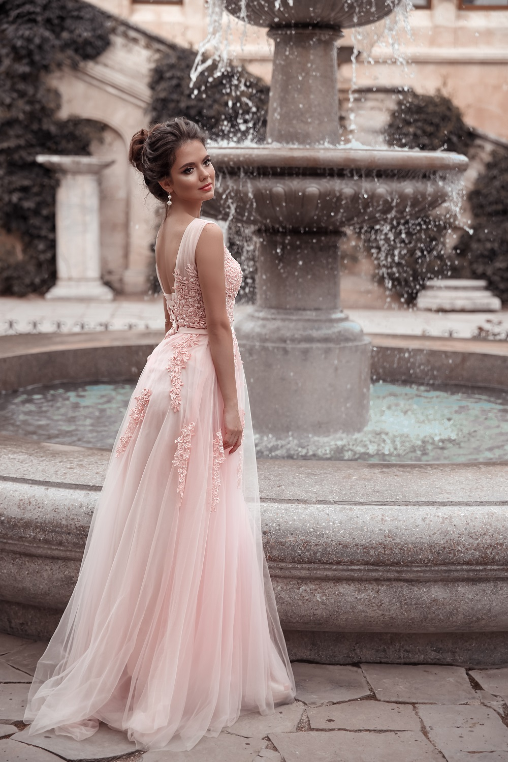 Beautiful bride in pink wedding dress. Outdoor romantic portrait of attractive brunette woman with hairstyle in prom dress with tulle skirt posing by fountain at park.